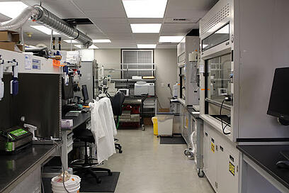 A view of the right side of the lab with computer work spaces, freeze driers, and ventilation hoods for working with material.