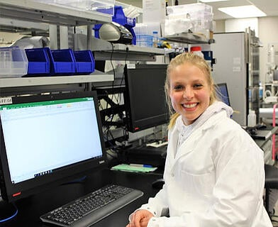 A picture of Kayla Owens, formulation scientist sitting in front of her computer in the lab.