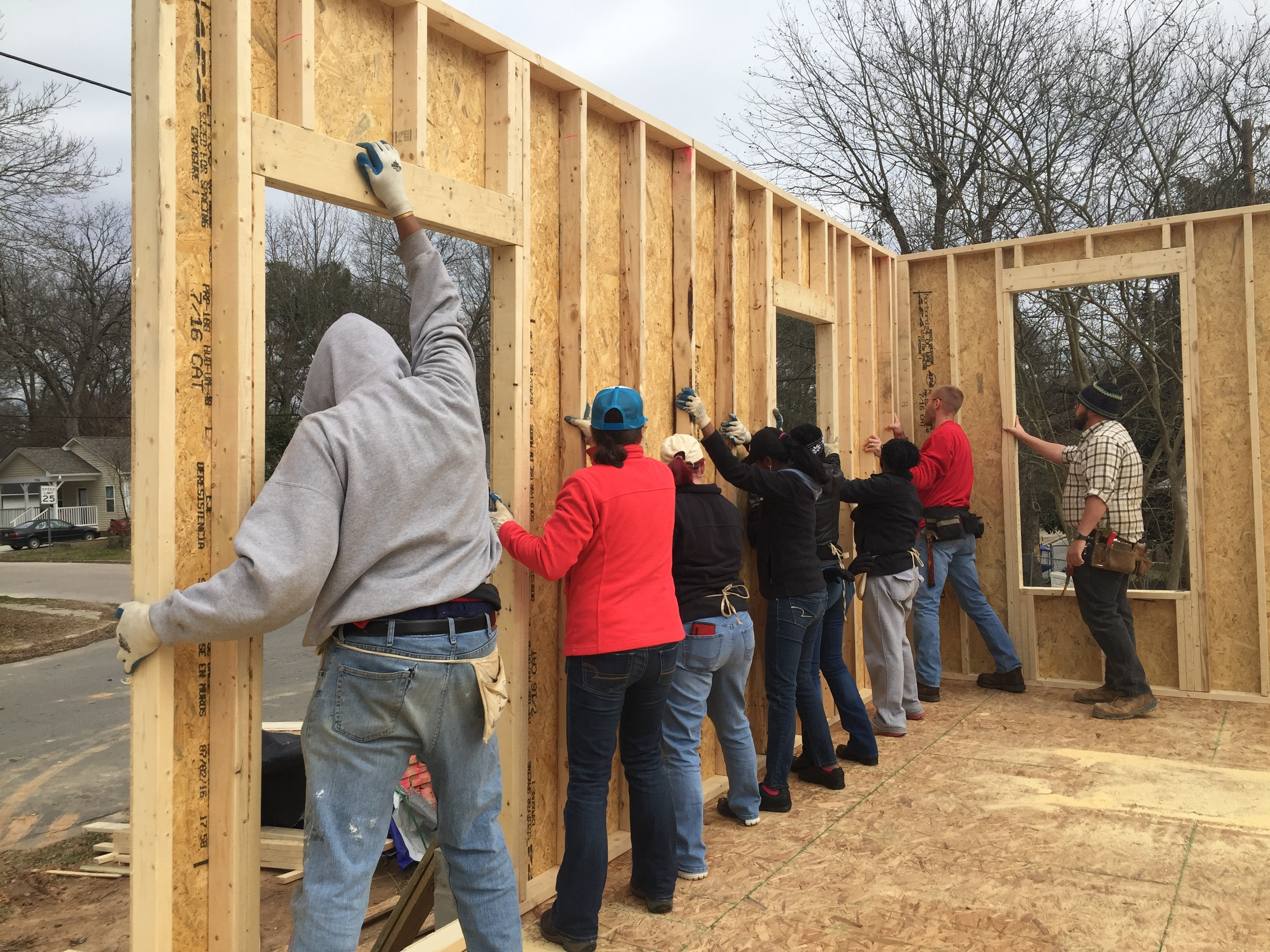 Six AgBiomers help raise walls on a habitat for humanity home along with Habitat volunteers.