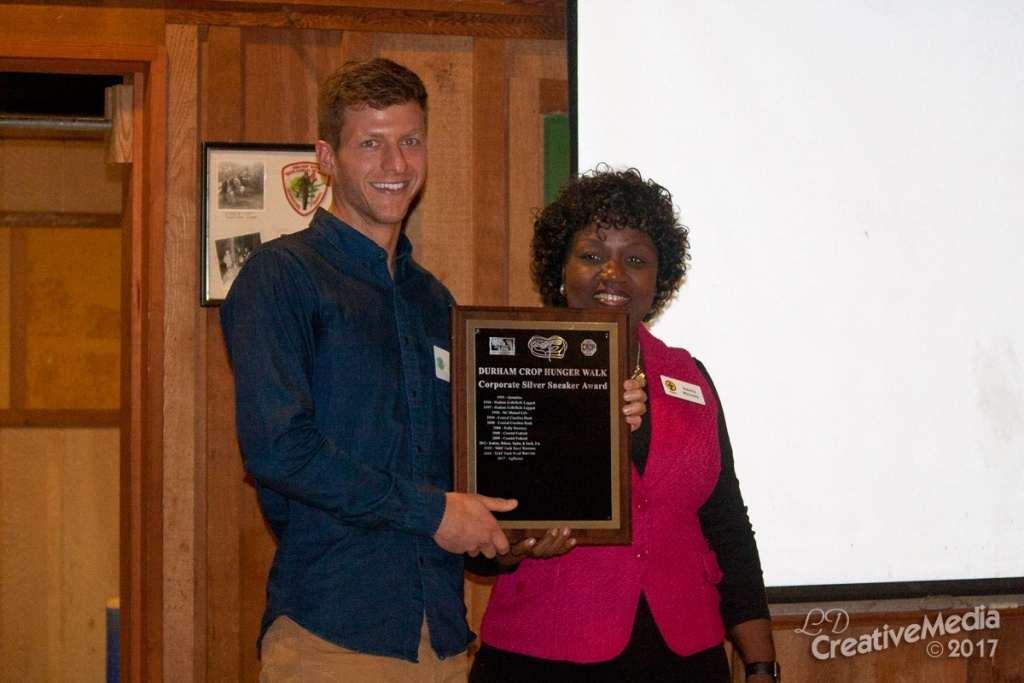 Dylan Kraus, an AgBiome Entomologist, receiving the silver sneaker award from the Durham Crop Walk.